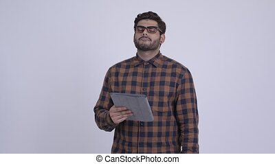Stressed young Indian hipster man using digital tablet and getting bad news