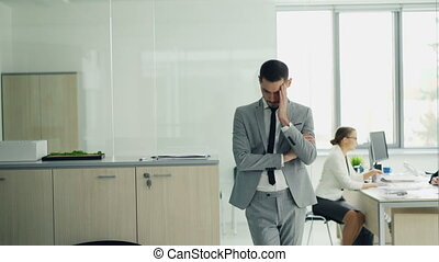 Stressed young man in suit is standing in office waiting for...