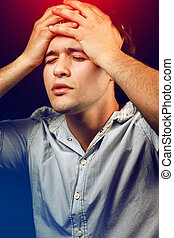 Stressed young man suffering from headache or hangover