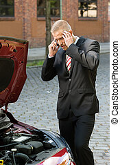 Stressed Young Man With His Breakdown Car Calling On Cellphone