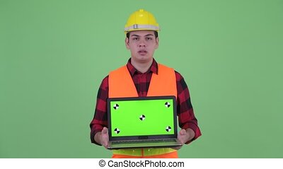 Stressed young multi ethnic man construction worker showing laptop