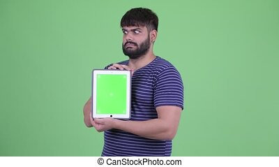 Stressed young overweight bearded Indian man showing digital tablet and getting bad news