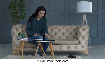Stressed young woman doing home accouting on sofa