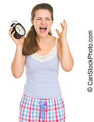 Stressed young woman in pajamas with ringing alarm clock