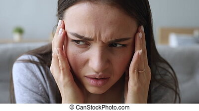 Stressed sick young woman suffering from migraine pain concept, upset girl beautiful female face touching temples coping with tension headache, high blood pressure or panic attack, close up view