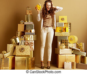 stressed young woman with yellow piggy bank with gold bow