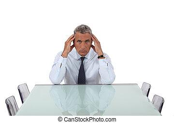 Stresses senior businessman sat in empty boardroom