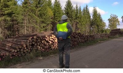 Stressful lumberjack on the forest road near logs