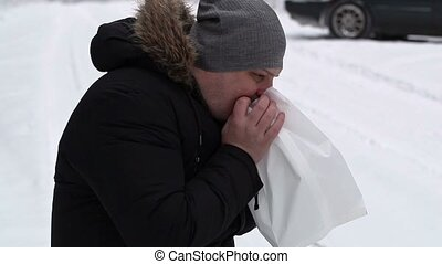 Stressful man breathe into paper bag on snowy road
