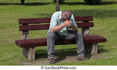 Stressful man in the park on bench
