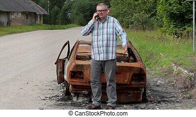 Stressful man talking on smart phone and kick car wreck
