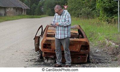 Stressful man using smart phone near burned down car wreck...