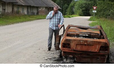 Stressful man walking near the car wreck and talking on...