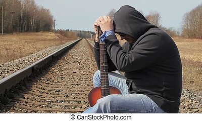 Stressful Man with guitar on the railway