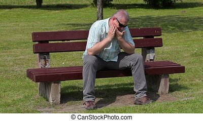 Stressful man with tooth pain in the park on bench