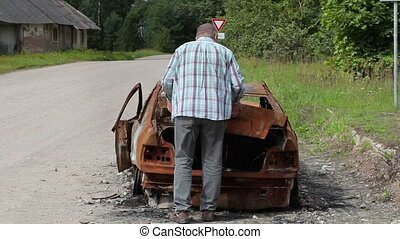 Stressful man worry near burned down car wreck on the side...