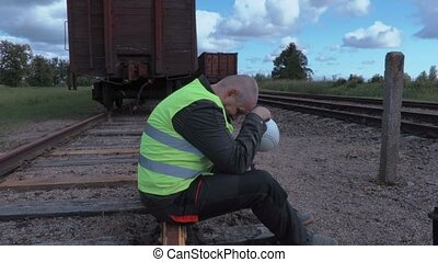 Stressful railway worker sitting on rails