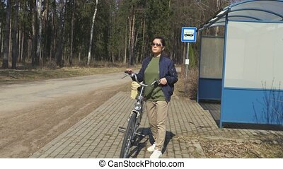 Stressful woman near bus stop with bicycle