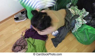 Stressful woman near pile of old clothes