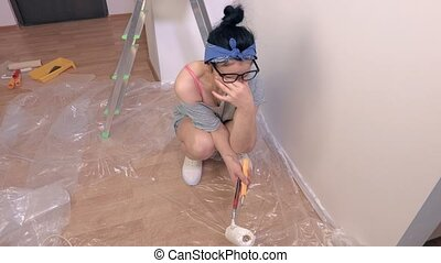 Stressful woman painter near wall