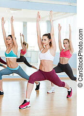 Stretch to the up! Three beautiful young women in sports clothing exercising together