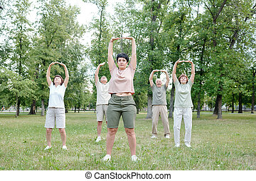 Stretching body at outdoor fitness class - Group of senior ...