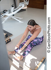 Brunette young plus size woman stretching on the floor
