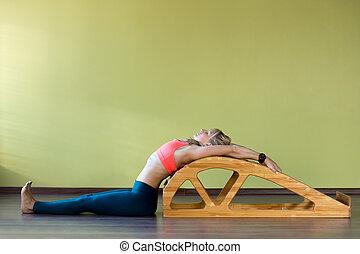 Stretching exercises on yoga backbend bench