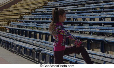 Stretching for legs and feet before the race in the stadium...