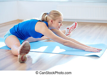 Portrait of happy young woman doing stretching exercise in gym