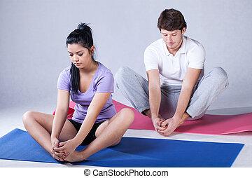 Stretching rehabilitation exercises - Young couple taking...