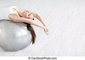 Stretching - Young girl with a ball in the studio