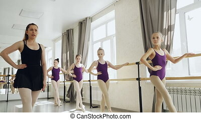 Strict ballet teacher is demonstrating legs and arms...