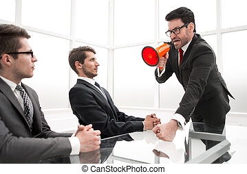 strict businessman with a megaphone at a meeting with employees.