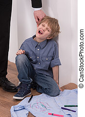 Strict father punishes naughty son. Isolated on white background boy sitting on floor