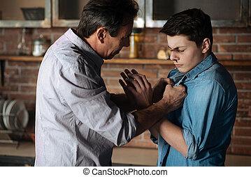 Strict father seizing shirt of his son