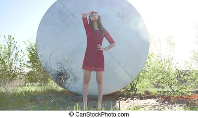 Strict girl. A serious girl stands near a barrel of petrol oil. An old barrel oil