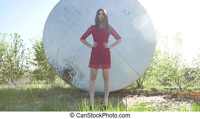 Strict girl. A serious girl stands near a barrel of petrol oil. An old oil barrel