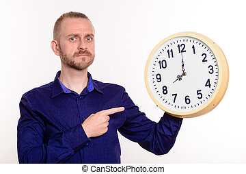 Strict man holding a large wall clock and points a finger at them