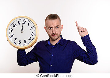Strict man holding a large wall clock and points a finger on empty space