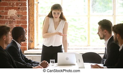 Strict woman boss reprimanding male employees, showing...