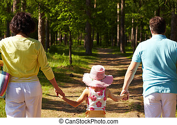 Stride - Back view of parents and their daughter walking in...