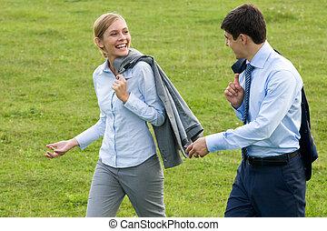 Stride - Rear view of associates walking down green grass...