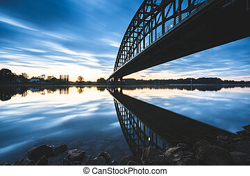 Striking arch bridge spans the river during the sunrise - ...