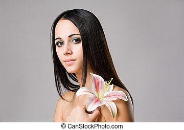 Striking brunette beauty with flower.