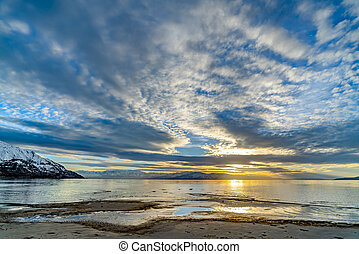 Striking cloudy sky over a calm lake that reflects the golden sun at sunset