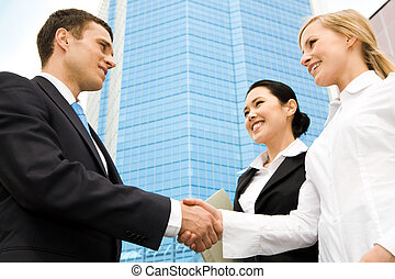 Striking deal - Image of successful partners handshaking at...