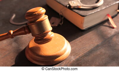 striking the gavel with book and handcuff on table .