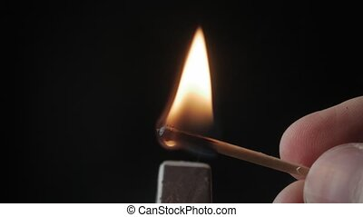 Striking wooden match and burning on black background.