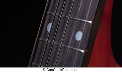 String of acoustic guitar, side view, on black, close up, slow motion